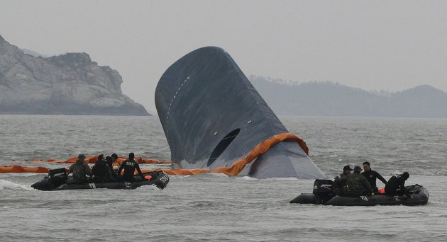 south-korean-coast-guard-officers-search-for-missing-passengers-aboard-a-sunken-ferry-in-the-waters-off-the-southern-coast-near-jindo-south-korea-on-thursday-april-17-2014-an-immediate-evacuation-order-was-not-issued-for-the-ferry-likely-with-scores-of-people-trapped-inside-because-officers-on-the-bridge-were-trying-to-stabilize-the-vessel-after-it-started-to-list-amid-confusion-and-chaos-a-crew-member-said-thursday