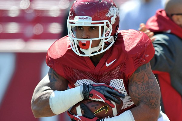 Arkansas running back Kody Walker runs drills during practice Saturday, April 5, 2014 at Razorback Stadium in Fayetteville.
