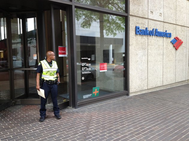 a-little-rock-police-officer-works-the-scene-after-a-robbery-at-the-bank-of-america-branch-at-200-w-capitol-ave-in-downtown-little-rock-on-friday-april-18-2014