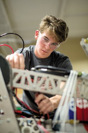 Joseph Walker, a senior on the Harding Academy robotics team, works on rewiring an arm on the team's robot. The team took the arm to use for spare parts at the team's most recent competition.
