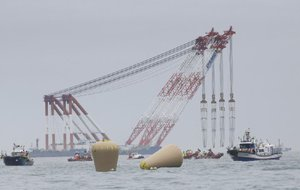 Cranes wait Friday near the buoys installed to mark the sunken ferry Sewol in the waters off the southern coast near Jindo, South Korea, after the last bit of the vessel's blue keel disappeared.