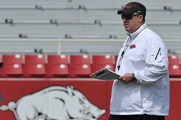 Arkansas coach Bret Bielema works with his team before the start of a football scrimmage Saturday, April 12, 2014 at Razorback Stadium in Fayetteville.