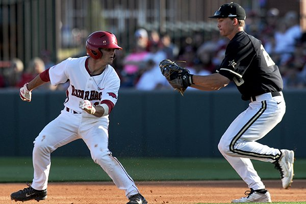 Arkansas right fielder Andrew Benintendi, left, moves to avoid the tag from Vanderbilt first baseman Bryan Reynolds during the first inning Saturday, April 19, 2014, at Baum Stadium in Fayetteville.