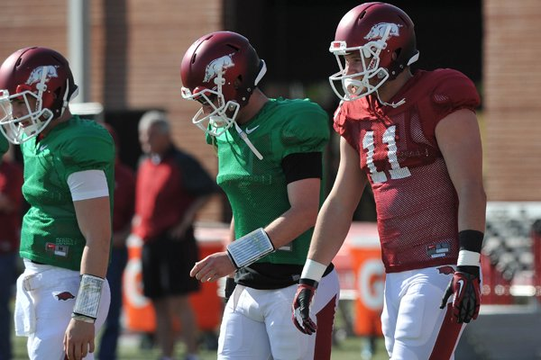 Arkansas tight end A.J. Derby (right) stretches out with teammates Brandon Allen (center) and others during the Razorbacks practice Thursday afternoon in Fayetteville.