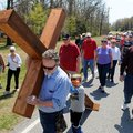 Worshipers walk behind Dale Richardson, left, and Cooper Mclean, 5, as they carry a large cross down...