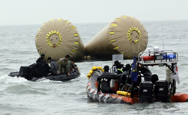 south-korean-rescue-members-search-passengers-believed-to-have-been-trapped-in-the-sunken-ferry-sewol-near-the-buoys-which-were-installed-to-mark-the-area-in-the-water-off-the-southern-coast-near-jindo-south-of-seoul-south-korea-saturday-april-19-2014-the-captain-of-the-sunken-south-korean-ferry-was-arrested-saturday-on-suspicion-of-negligence-and-abandoning-people-in-need-as-investigators-looked-into-whether-his-evacuation-order-came-too-late-to-save-lives-two-crew-members-were-also-arrested-a-prosecutor-said