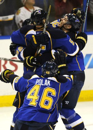 St. Louis Blues defenseman Barret Jackman (5) is congratulated by teammates Adam Cracknell (right) and Roman Polak (46) after scoring the game-winning goal against the Chicago Blackhawks in overtime of their first-round NHL playoff game Saturday in St. Louis. The Blues won 4-3 and took a 2-0 series lead.