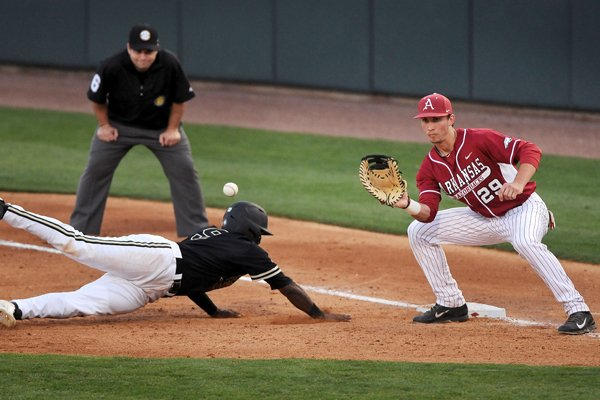 Vanderbilt runner Xavier Turner dives back safe to first ahead of a pickoff throw to Arkansas first baseman Eric Fisher during the game on Friday April 18, 2014, in Baum Stadium.