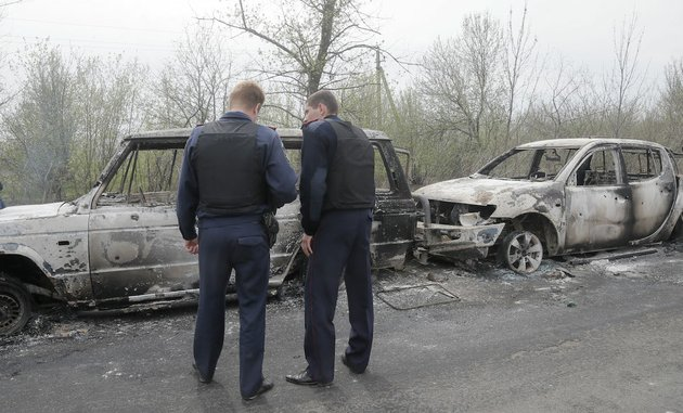 local-police-officers-inspect-burnt-out-cars-after-a-night-fight-at-the-check-point-which-is-under-the-control-of-pro-russian-activists-in-the-village-of-bulbasika-near-slovyansk-ukraine-sunday-april-20-2014-at-least-one-person-was-killed-pro-russian-insurgents-defiantly-refused-to-surrender-their-weapons-or-give-up-government-buildings-in-eastern-ukraine-despite-a-diplomatic-accord-reached-in-geneva-and-overtures-from-the-government-in-kiev