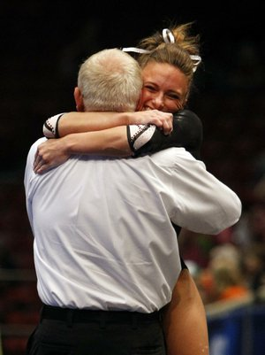 Arkansas' Katherine Grable, right, celebrates with coach Mark Cook after competing on the vault during the individual competition at the NCAA college women's gymnastics championships on Sunday, April 20, 2014, in Birmingham, Ala. (AP Photo/Butch Dill)