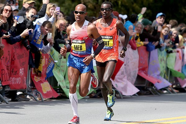 Meb Keflezighi, of the United States, leads Josphat Boit, also from the United States, passed Wellesley College during the 118th Boston Marathon Monday, April 21, 2014 in Wellesley. (AP Photo/Mary Schwalm)