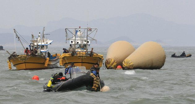 south-korean-rescue-team-members-work-to-rescue-passengers-believed-to-have-been-trapped-in-the-sunken-ferry-sewol-near-the-buoys-which-were-installed-to-mark-the-vessel-in-the-water-off-the-southern-coast-near-jindo-south-korea-on-monday-april-21-2014