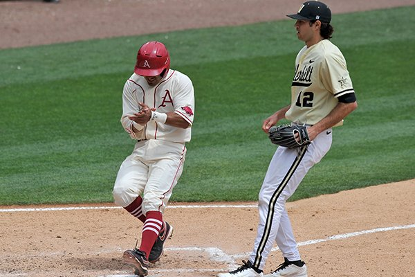 Arkansas baserunner Michael Bernal scores a run as Vanderbilt pitcher Adam Ravenelle covers the plate on a wild pitch in the fifth inning of Sunday afternoon's game at Baum Stadium in Fayetteville.