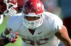 Arkansas defensive end Trey Flowers runs through a drill during practice Tuesday, April 22, 2014 in Fayetteville.
