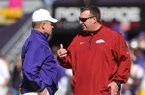 Arkansas coach Bret Bielema, right, and LSU coach Les Miles talk before a game Nov. 29, 2013 at Tiger Stadium in Baton Rouge, La.