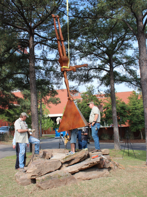 "Crews work to install ""Cecil,"" a new sculpture of a man doing a one-armed handstand, Thursday at Riverfront Park in Little Rock."