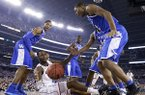 Connecticut forward Phillip Nolan, center, loses the ball between Kentucky's Andrew Harrison, left, and Aaron Harrison, right, during the second half of the NCAA Final Four tournament college basketball championship game Monday, April 7, 2014, in Arlington, Texas. (AP Photo/Eric Gay)