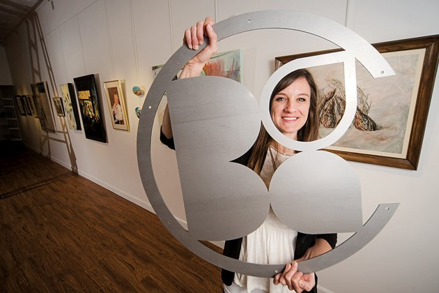 the-batesville-area-arts-council-has-moved-to-a-new-space-on-main-street-and-has-a-new-director-paige-dirksen-above-who-holds-an-aluminum-version-of-the-batesville-arts-council-logo-that-will-hang-in-the-gallery
