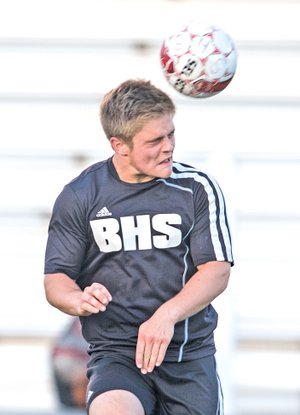 STAFF PHOTO ANTHONY REYES Bennett Moehring, Bentonville junior, heads the ball against Springdale on Friday at Bulldog Stadium in Springdale.