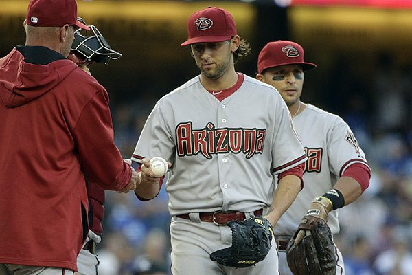 Arizona Diamondbacks starting pitcher Mike Bolsinger, center, hands the ball to manager Kirk Gibson, left, during the fifth inning of a baseball game against the Los Angeles Dodgers, Saturday, April 19, 2014, in Los Angeles. (AP Photo/Jae C. Hong)