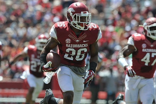 Arkansas defender Rohan Gaines returns an interception for a touchdown during the Red-White game Saturday afternoon at Razorback Stadium in Fayetteville.