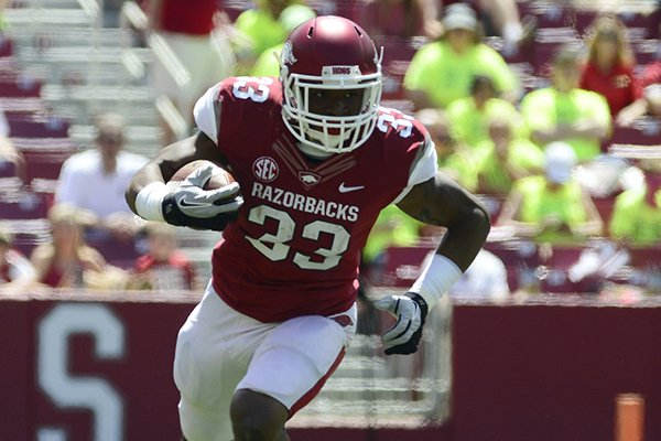 Arkansas running back Korliss Marshall (33) runs the ball during their spring NCAA college football game, Saturday, April 26, 2014, in Fayetteville, Ark. (AP Photo/Sarah Bentham)