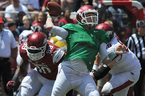 Arkansas quarterback Austin Allen passes the ball while being rushed by defensive end Brandon Lewis (99) during Saturday's Red-White Game at Razorback Stadium in Fayetteville.