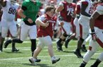 Lifelong Arkansas Razorbacks fan Canaan Sandy runs the ball for a touchdown Saturday afternoon during the Red-White Game at Razorback Stadium in Fayetteville.
