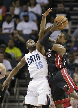 Miami Heat's Mario Chalmers, right, shoots over Charlotte Bobcats' Kemba Walker, left, during the first half in Game 4 of an opening-round NBA basketball playoff series in Charlotte, N.C., Monday, April 28, 2014. (AP Photo/Chuck Burton)