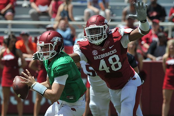 Arkansas defender Deatrich Wise Jr. puts pressure on quarterback Rafe Peavey during the Red-White game Saturday afternoon at Razorback Stadium in Fayetteville.