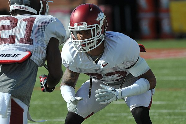 Arkansas cornerbacks Tevin Mitchel (23) and Carroll Washington (21) run drills during practice Thursday afternoon in Fayetteville.