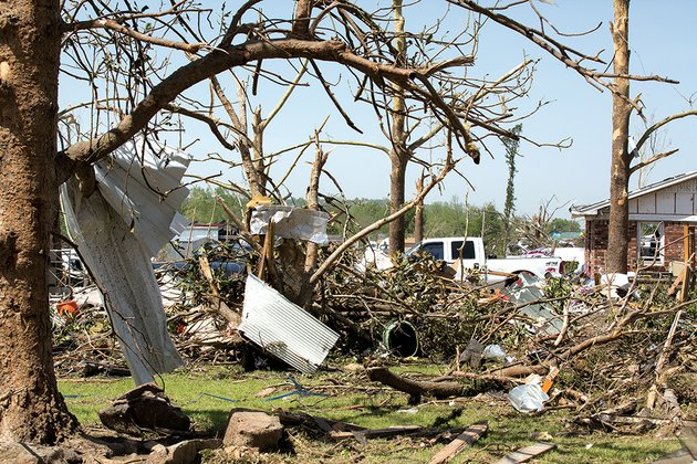 sheet-metal-hangs-from-a-tree-in-mayflower-near-damaged-homes-and-businesses-a-tornado-cut-a-swath-of-destruction-through-the-community-killing-three-people-mayor-randy-holland-said-offers-of-support-have-poured-in-from-people-all-over-arkansas