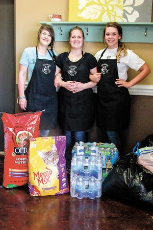From left, Ashley Wilkerson, Laura Waller and Bailee Uhiren stand with some of the donations they collected at Grinds Coffee Co. in Cabot.