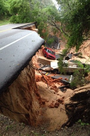 Vehicles sit amid collapsed pavement Wednesday after heavy rains washed a segment of a scenic highway into a ravine near Pensacola, Fla.