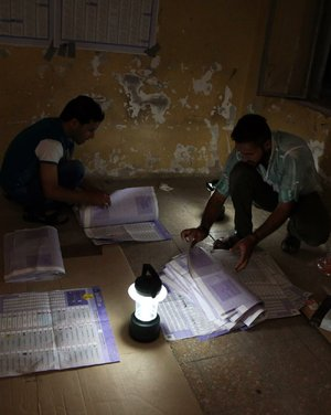 Electoral workers at a polling center in Baghdad count ballots Wednesday under lamplight after power was cut to the building.
