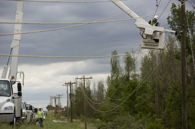 journeyman-technician-grant-pugh-of-bbc-electric-hangs-rope-to-new-poles-to-guide-the-stringing-of-power-lines-wednesday-in-mayflower-where-sundays-tornado-tore-out-the-lines