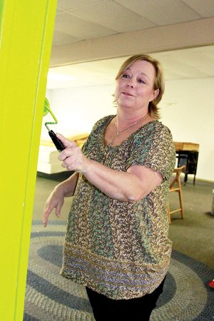 Julie Bohannan paints the interior of the new Cabot Community Outreach Thrift Store.