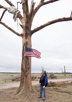 Preston Scroggin of Vilonia looks at the flag he had installed Monday after the April 27 tornado blew away his home, barn and outbuildings on what he calls the south farm, where he has lived since 1980. Scroggin said the flag makes the statement that Vilonia is strong and will rise again. The tree was one of only three of his that survived the April 25, 2011, tornado, he said, but the tree was heavily damaged this time. Scroggin, a former Faulkner County judge, is director of the Arkansas Livestock and Poultry Commission.