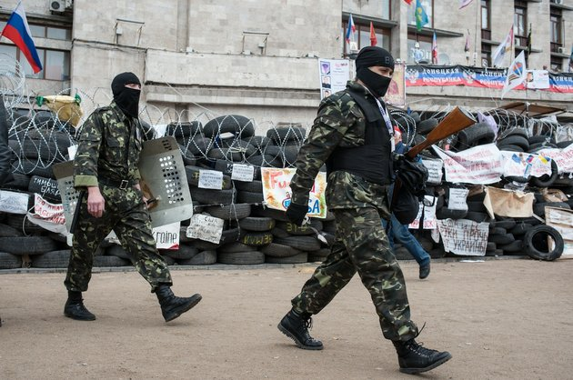 pro-russian-activists-walk-by-a-barricade-at-the-regional-administration-building-in-donetsk-ukraine-friday-may-2-2014-ukraine-launched-what-appeared-to-be-its-first-major-assault-against-pro-russian-forces-who-have-seized-government-buildings-in-the-countrys-east-with-fighting-breaking-out-friday-in-slovyansk-that-has-become-the-focus-of-the-insurgency