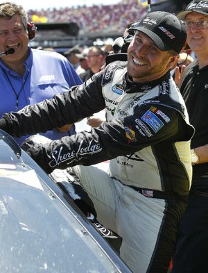Brian Scott climbs from his car Saturday after winning the pole for today's NASCAR Sprint Cup Aaron's 499 at Talladega (Ala.) Superspeedway.
