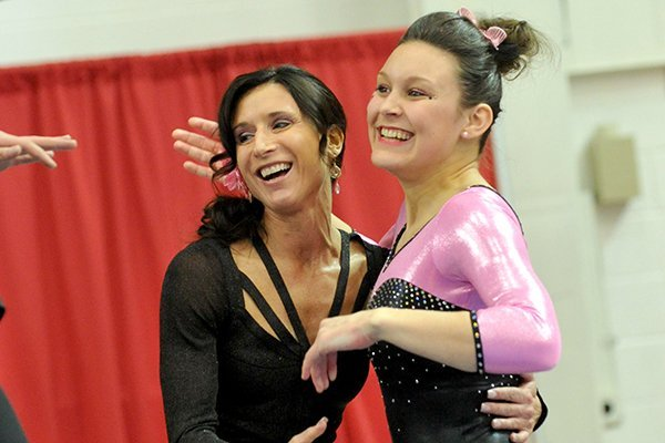 Arkansas gymnastics co-head coach Rene Lyst embraces gymnast Sydnie Dillard after she competed on the beam during a meet against Florida on Friday, Feb. 1, 2013 at Barnhill Arena in Fayetteville.