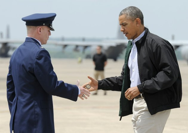 president-barack-obama-shakes-hands-with-col-patrick-rhatigan-commander-19th-airlift-wing-little-rock-afb-and-gives-him-a-challenge-coin-after-obama-arrives-at-little-rock-air-force-base-on-wednesday-may-7-2014-obama-is-visiting-with-first-responders-and-families-affected-by-the-recent-tornadoes