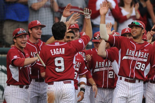 Arkansas designated hitter Clark Eagan (9) is congratulated by his teammates after hitting a solo home run against Texas A&M during the third inning Friday, May 9, 2014, at Baum Stadium in Fayetteville.