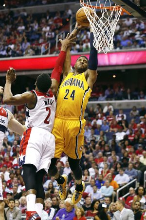 Indiana Pacers forward Paul George (24) shoots for two points under pressure from Washington Wizards guard John Wall (2) during the second half of Game 3 of an Eastern Conference semifinal NBA basketball playoff game in Washington, Friday, May 9, 2014. (AP Photo/Alex Brandon)