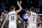 Brooklyn Nets guard Shaun Livingston (14) and guard Joe Johnson (7) high-five as they walk to the bench during timeout in the fourth quarter against the Miami Heat during Game 3 of an Eastern Conference semifinal NBA playoff basketball game on Saturday, May 10, 2014, in New York. The Nets won 104-90. (AP Photo/Julie Jacobson)