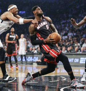 Miami Heat forward LeBron James gets fouled from behind by Brooklyn's Paul Pierce in the Nets' 104-90 victory Saturday night. James scored 28 points and grabbed 8 rebounds while Pierce had 14 points and 4 rebounds.