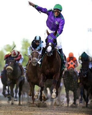 FILE - In this May 3, 2014, file photo, jockey Victor Espinoza celebrates aboard California Chrome after winning the 140th running of the Kentucky Derby horse race at Churchill Downs in Louisville, Ky. The California colt will be running in the Preakness with a bulls-eye on his back as perhaps racing's next superstar. He figures to face eight or nine rivals in the middle leg of the Triple Crown series, and one of them might be a filly.  (AP Photo/David J. Phillip, File)