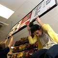 STAFF PHOTO FLIP PUTTHOFF SIGN OF SUMMER Cassie Pierson, right, balances a price sign on Thursday ...