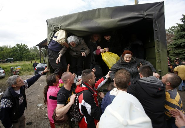 people-help-old-women-out-of-a-military-truck-during-evacuation-from-obrenovac-some-18-miles-southwest-of-belgrade-serbia-saturday-may-17-2014-record-flooding-in-the-balkans-leaves-at-least-20-people-dead-in-serbia-and-bosnia-and-is-forcing-tens-of-thousands-to-flee-their-homes-meteorologists-say-the-flooding-is-the-worst-since-records-began-120-years-ago