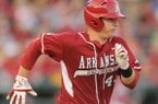 Arkansas catcher Alex Gosser heads to first after hitting the ball against Texas A&M during the fourth inning Friday, May 9, 2014, at Baum Stadium in Fayetteville.
